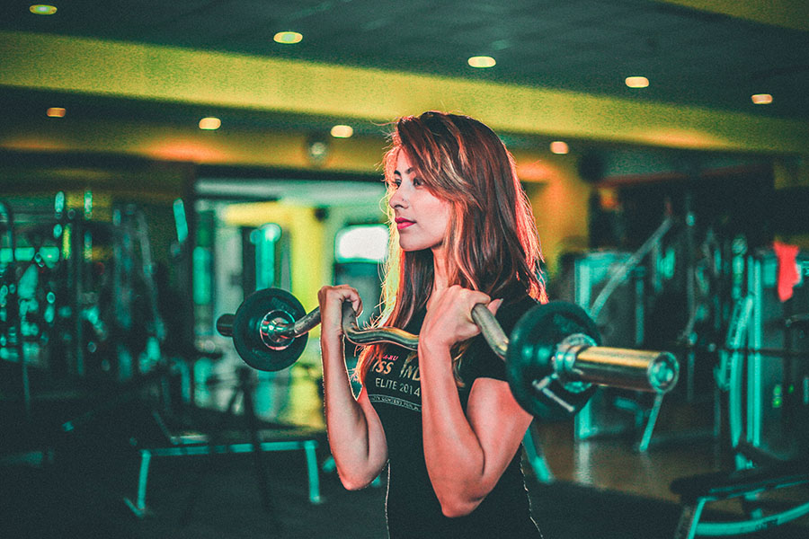 LinkedIn Profile for B2B. A woman with a black teeshirt and long brown hair lifting deadweights in a professional gym.