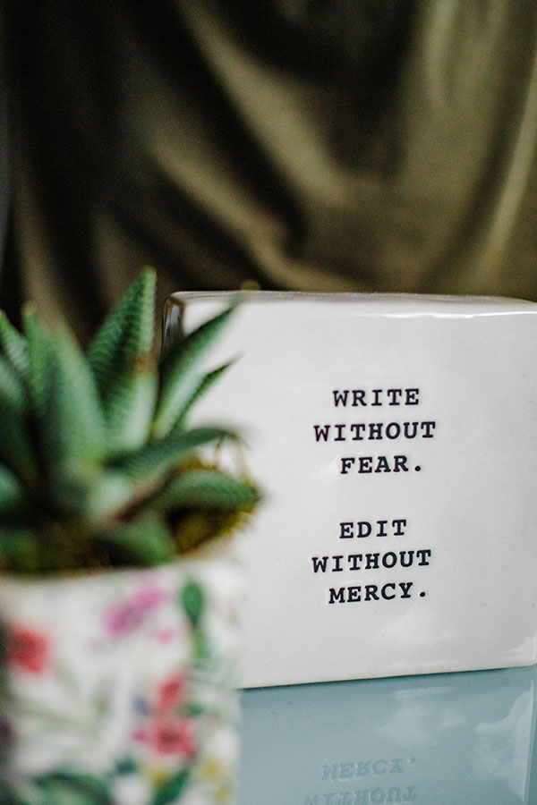 Blogging 101, reads write without fear. Edit without mercy on a ceramic tile with an unfocused potted plant in the foreground.