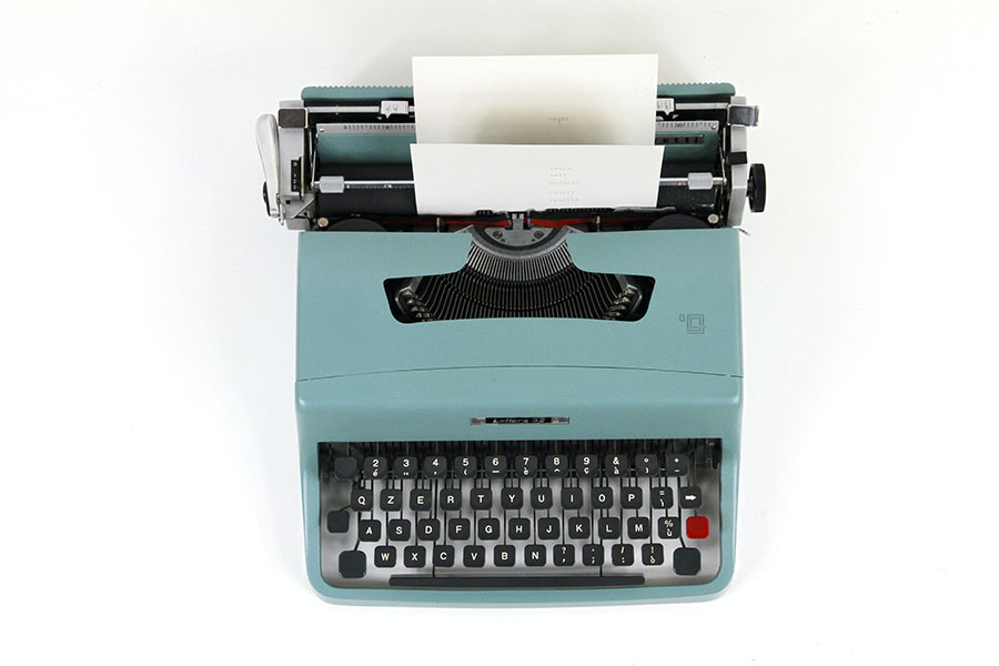 Blogging 101, an image of a mid century style typewriter from above, teal in color with a white background.