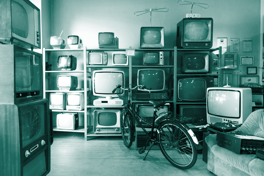 marketing trends for 2021 shows an image of a wall of old televisions in all sizes and shapes. A bike is parked in front like it might be a pawn shop.