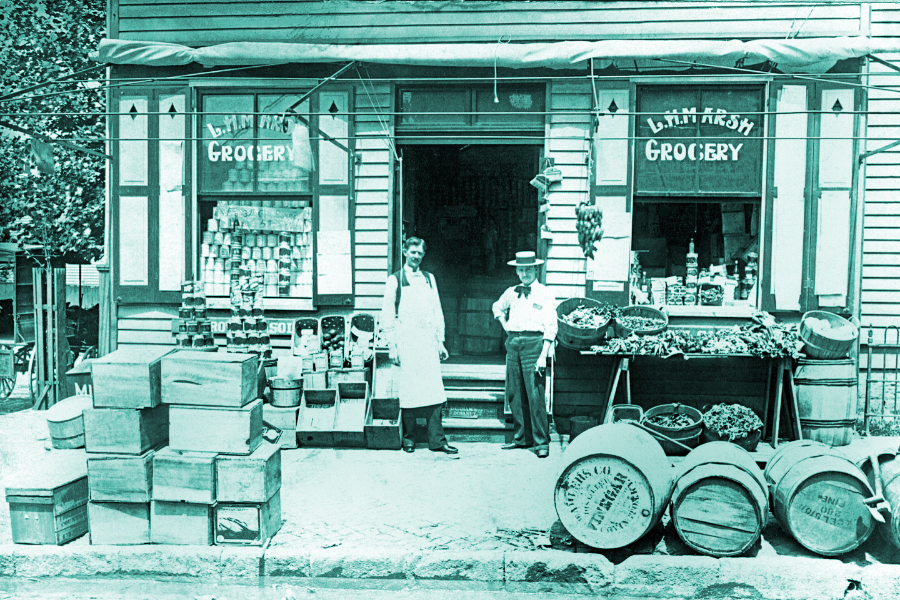 social media campaign, image is of an old country story with boxes and barrels piled out front and the two owners standing in the doorway.