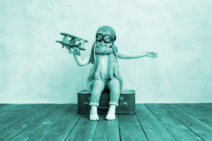 Innocent Archetype: showing a small boy wearing old aviator goggles and holding a toy plane.