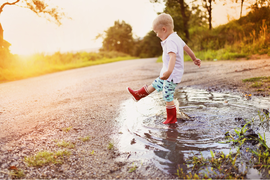 Innocent Archetype. Young boy splashing in a puddle with rain boots on.
