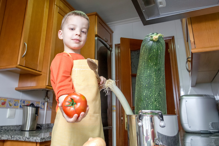reusing content: shows a young boy in the kitchen with an apron on, getting ready to cook a zucchini that's almost as big as he is.