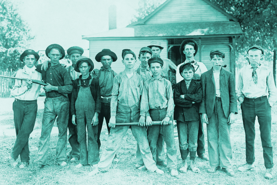 Promoting Your Community, showing a group of young men from the late 1800's standing together looking serious in front of an old house.
